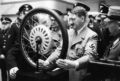 Eröffnung der Internationalen Automobil– und Motorrad-Ausstellung in Berlin am 20. Februar 1937: Hitler, bei seinem Rundgang durch die Messehallen am Kaiserdamm in Charlottenburg, vor dem Modell eines Rades; rechts NSKK-Führer Adolf Hühnlein.
