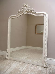 Circa 1900 Large French antique rococo style mirror painted in cream. Featuring a beautiful crest at the top with shells, flowers, leaves and scrolls with rounded shoulders. The frame has a decorative repeating pattern and beading surrounding the mirror.