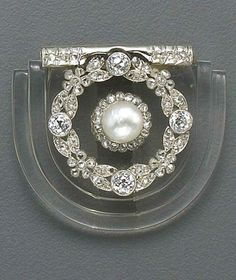 A belle époque rock crystal, diamond and platinum brooch, French, circa 1910 the rock crystal step-like panel centering a rose-cut diamond and cultured pearl cluster within a wreath of rose and old European-cut diamonds; with French assay marks; estimated total diamond weight: 1.05 carats; width: 1¼in.