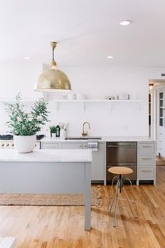 Minimalist kitchen with a large gold industrial pendant light, and gray cabinents