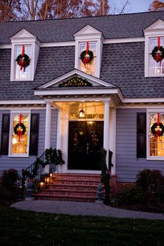 Wreaths hanging by a red ribbon on each window