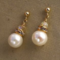 Simple white freshwater pearls are hand wire wrapped onto 14k gold filled posts. Accented with a gold Swarovski rhinestone crown. Elegant, simple and perfect for everyday. Earring Details: - Freshwater pearl is 7 mm - Pearls earrings with the posts are about 1 inch long (2.54 cm) -