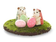1. Use a foam paintbrush to apply one to two coats of acrylic paint to regular or Ceramic Eggs (from $14 per dozen; CeramicEggs.com); let dry. 2. Use a small paintbrush and white acrylic paint to add clusters of small dots. (Hedgehogs, $19.96 for set of 4, and Mossy Mat, from $7.99; WorldMarket.com)