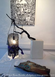 Lampe ucpcycling en béton, grillage, bois et dentelle pvc Un lampion en grillage est habillé de dentelle en pvc noir, détournée d'un set de table. Un ruban en satin violet apporte une touche colorée. Suspendu à une branche calcinée, joliement noircie...