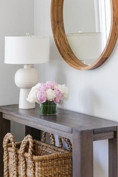 A round wood mirror stands over a brown console table topped with a white lamp as well as a woven basket tucked underneath.