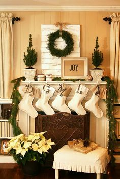 50 Gorgeous Christmas Holiday Mantel Decorating Ideas (just saw those Stockings with large initials, by Mudpie!) I really like the pallet board behind the wreath