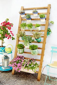 Make this living wall from a $34 handrail. Start by finishing the railing with a coat of exterior stain. Then prep you pots by wrapping them with twine to attach them to the handrail. Put it all together by hammering nails into the handrail and attaching pots by tying twine around nails. Click through for the full instructions.