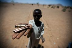 27 March 2011. Rounyn: A child collects bullets from the ground in Rounyn, a village located about 15 km north of Shangil Tobaya, North Darfur. Most of the population in Rounyn recently fled to camps for displaced people due to the clashes between the Government and the armed movements.  Photo by Albert Gonzalez Farran / UNAMID - www.albertgonzalez.net