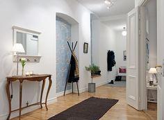wzorzysta tapeta,wnęki w scianach,stylowa konsolka,wieszak czarny nowoczesny,wąski przedpokój,biały przedpokój,korytarz,jak urzadzić wąski korytarz,biale ściany,skandynawski styl,nowoczesne mieszkanie,dekoracja holu,dekoracje do przedpokoju,typografie,czarny chodnik,dywan w przedpokoju,biała podłoga