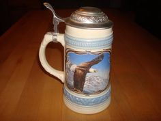 Vintage Gerz German Eagle Lidded Stein Ceramic. This is in really nice condition with some signs of wear no chips or cracks. Beautiful stein has a eagle head on one side and the other side has the eagle in flight. Stein has a 95% zinn lid, stamped on the inside of lid. Very beautiful piece for any collection. Stein is 7 3/4 tall with the lever on the lid and 5 3/4 wide with the handle. Gerz Germany stamped on bottom.