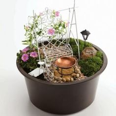 """White Fairy Garden - The white fairy garden starter set includes a plastic container that measures 12"""" x 6"""" along with a white wire swing, copper bird bath, white wire bicycle and coach lamp. This table top fairy garden is perfect for the beginning gardener or children (under adult supervision). Five piece set does not include flowers or landscaping materials shown in the photo. Those items should be purchased separately."""