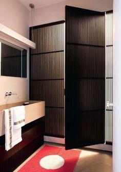 Dans la salle de bains, on retrouve une vasque en pierre, et une douche masquée par un claustra en chêne teinté. Plus de photos sur Côté Maison  http://petitlien.fr/7a44