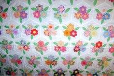 I'd like to ID this quilt top.  Marked 'Flower Garden' but I haven't been able to verify that. It has 3 hexagon flowers with 3 leaves appliqued onto a white hex, and joined with sashes to other hex pieces.  Thanks!