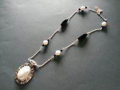 Collana con agata bianca, onice e ciondolo in agata bianca striata, montata con componenti e catena in metallo color argento. Realizzazione artigianale.