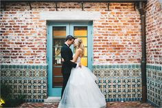 intimate moment between newlyweds in front of blue door and brick wall