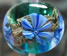 """""""This is soft glass built on a 1/16th rod. It's size is 16 mm by 14 mm at the hole. It was created on July 1, 2013 at approximately 2 AM."""" by Allan"""