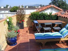A small, rooftop terrace provides the perfect place to take in the great outdoors. Terra-cotta pavers, Spanish tiles and stunning mountain views transport guests on a Mediterranean retreat. Potted herbs and shrubs enhance the Tuscan feel of the space. Design by Joan Grabel