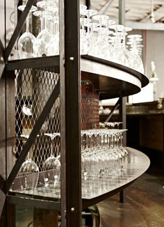 The leather top main bar, clad in pressed tin ceiling panels, is located symmetrically in front of the roaster shelving. Purpose designed overstuffed, leather and steel, chairs, barstools and copper clad tables create a formal raised dining area in front of the bar. A series of 5 horseshoe shaped, deep buttoned, high backed, banquet seats run down the right hand wall of the space. Each private banquet seat surrounds a leather clad, long, narrow, profile cut steel table.