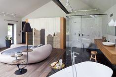 Połączona przestrzeń sypialni i łazienki to rozwiązanie chętnie wybierane w dużych mieszkaniach, czyli tam gdzie są przynajmniej dwie łazienki - jedna dostępna dla pozostałych domowników i gości. Skoro na co dzień mamy tak mało czasu dla siebie, przy takiej aranżacji wnętrza możemy być ze sobą wykonując zwykłe czynności.  Dzięki powiększeniu przestrzeni sypialni pojawiło się miejsce na niecodzienne łóżko, zajmujące środek pokoju.
