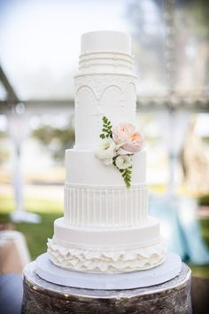 All white wedding cake with raised icing patterns and detail. Love the small and subtle pop of color with the flowers. Stunning