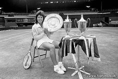 Billie Jean King of the United States on the Centre Court at Wimbledon with the three trophies she won at the 1973 championships. King won the singles trophy, and the women's and mixed doubles