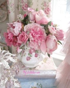 Pink roses and other flowers in a beautiful teapot