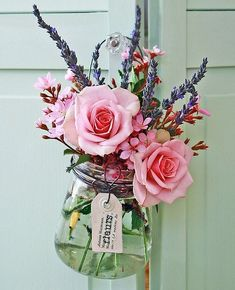 pink and aqua: pink roses hanging on an aqua door