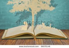 Paper cut of children read a book under tree on old book by jannoon028, via ShutterStock