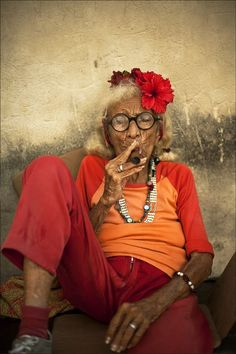 A relaxing cigar in the afternoon ... and flowers in the hair ... Life is worth living. Graciela - The Cigar Lady - Havana, Cuba