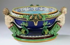 """Majolica wine cistern, attributed to Minton, circa 1875, likely modeled by Pierre-Emile Jeannest, of oval form with a robin's egg blue reeded removable liner centering an oval scrollwork reserve and having a band of foliate scrollwork at the rim, the body of the cistern flanked by cherubic term figures ending in green acanthus leaves, and ram's heads with green grape leaves and tendrils on a cobalt ground, the whole resting on a stepped molded plinth, unmarked, 17""""h x 35""""l x 28""""w."""