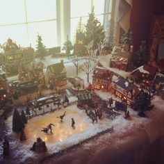 """Christmas village decorated using Dickens Village houses from Department 56. We made tiers out of insulating foam (the pink foam stuff...NOT actual insulation) and left a hole for the """"lake"""", which is a piece of glass covered with Jack Frost ice and glass glitter, and is sitting above LED string lights."""