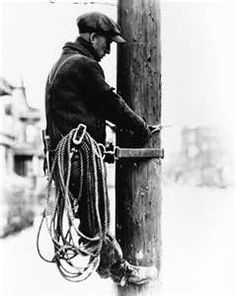 telephone lineman works on a pole. Location and date unknown.
