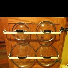 Rack for pot lids made by installing cheap curtain rods to the inside of lower cabinet doors. by connie