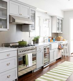 light gray-painted cabinets and glass inserts for upper cabinets