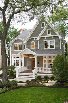 Beautiful traditional grey colonial house with white trim, white columns, white porch railing, transom windows, eyebrow dormer