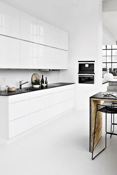 Shiny white kitchen with white walls and floors to match.
