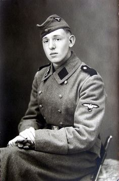 An early SS-VT (SS-Verfügungstruppe) studio portrait showing all the hallmarks of the early Waffen-SS uniform to include the pointed shoulder boards, SS eagle in triangle on the side cap, early skull button on the side cap, numbered SS collar tab and striped piped collar.