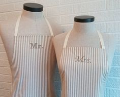 Eat in or entertain together more often with a matching apron set! Makes a wonderful wedding or shower gift, or anniversary gift! These Husband and Wife aprons are made from a medium-weight cotton fabric in an ivory and khaki stripe. Ivory ribbon for the neck and waist ties. Hers features a ruffled bottom. Both aprons have a pocket. Aprons are machine washable. Mr and Mrs embroideries are done in khaki thread. Please let me know if you would like a different embroidery color.  PERSONALIZE…