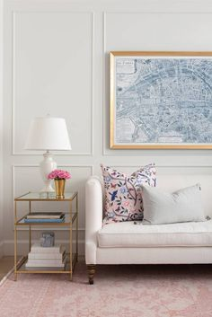 Gold and white is a color combination that seems to be enjoying it's time in the spotlight, and this is a fine example! The custom frame in this vignette is the star of the space, thanks to the white walls, sofa and accessories, while the tone and lines of the side table mimic that of the moulding. A lovely space!