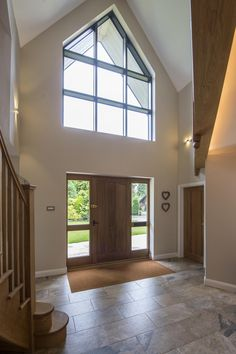 Once inside the large open hallway is lit up by the shaped apex frame #glazing #aluminium #bespoke #shapedwindow #apex #curtainwalling #entrance #hallway #express #renovation #traditional