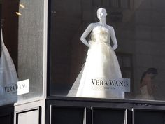 A girl in a Vera Wang wedding gown near a mannequin displaying another one. On Newbury Street.     mg