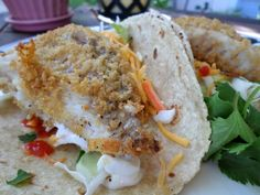 Fish Tacos... panko-crusted white fish is baked in the oven until crispy, then rolled up in a tortilla with cabbage, cheese, ranch dressing, cilantro, and sriracha!