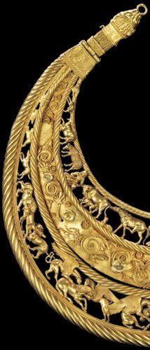 "Scythian pectoral from between the 6th & 4th centuries BCE discovered in a tumulus in the Ukraine. The crescent-shaped pectoral has a well-balanced composition which is symmetrical but not rigidly so. The ends of the crescent that come close together are decorated with stylized lion heads holding rings in their mouths; these rings served as clasps. The pectoral is divided into three ""tiers"" or bands with gold braids framing each ""tier."""