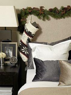 En grangirlander med kongler og reinsdyr pryder sengegavlen, og en strikket julestrømpe henger ned på siden. Styling: Tone Kroken.