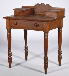 """Vernacular dressing table attr. Kentucky, cherry and poplar, shaped backsplash over two glove drawers, rectangular top over single long drawer with round wood pulls, all on four turned legs. 37"""" H x 28"""" W x 20"""" D. Circa 1840."""