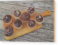 Chocolate Cupcakes Rustic wood print. Delicious decorated chocolate cupcakes on a handled cutting board with rustic wood table background. Cupcake art wood print for kitchen, bakery, cafe or gift. Original work available as framed print, canvas, greeting card and more only on Fine Art America and Pixels.com. https://andrea-rea.pixels.com/