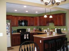 Dark cabients, Green wall paint, black appliances.  , Kitchens Design