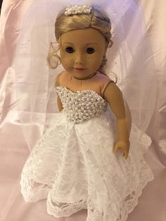 This is modern style wedding gown for American Girl Dolls or any 18 inch doll. The dress is white satin with a lace over skirt and a lace trim at the hem. It has a sleeveless bodice that has been hand beaded with pearls, clear beads and silver beads. The dress comes with crinoline and a hand beaded veil. It has a Velcro closure in the back. The shoes and pants are not included.