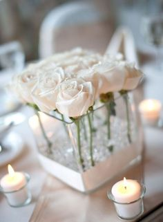 A simple white centerpiece using roses, diamond confetti and votive candles.