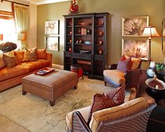 A living room in autumnal colors. Old gold walls, pumpkin  orange sofa, tan carpet and a lot of autumn ornaments: orange pillows, armchairs in different nuances of brown and orange, camel carpet, pictures with paintings like flames, in the color of fire, a big orange and green bunch of autumn flowers and a seal brown library make the room appear cozy and relaxing.